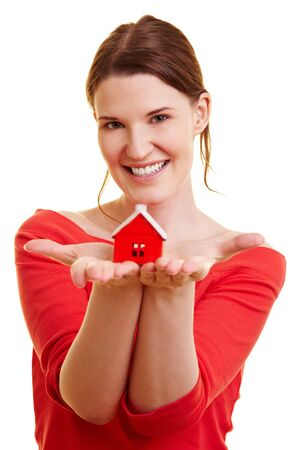 Happy woman holding a little red house in her hands Stock Photo - 7360316
