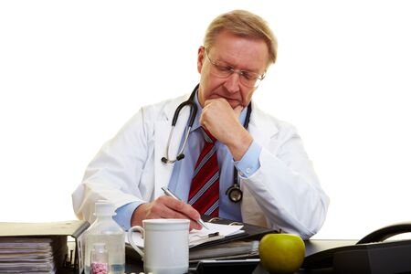 Physician sitting at a desk and taking notes Stock Photo - 7501480