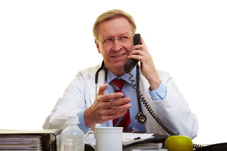 Physician sitting at a desk and talking on the phone Stock Photo - 7501484