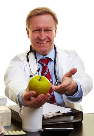Happy senior doctor offering a green apple photo