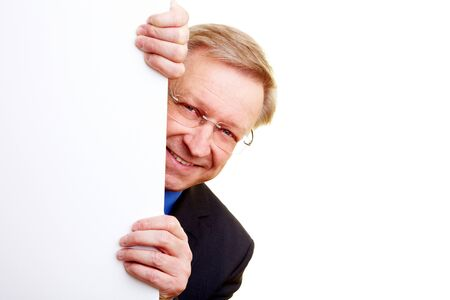 Happy senior businessman peeking behind a white wall Stock Photo - 7501474