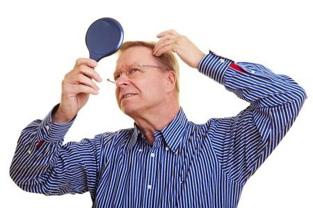 人間の髪の毛: 鏡の中の彼の後退ヘアラインを見ている高齢者の男