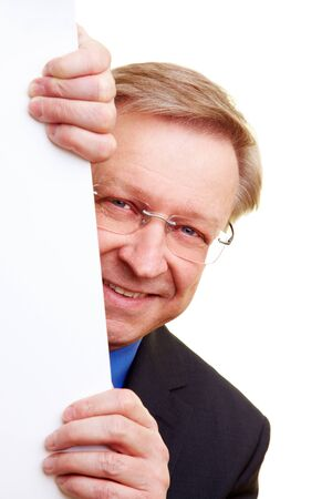 Happy senior businessman peeking behind a white wall photo