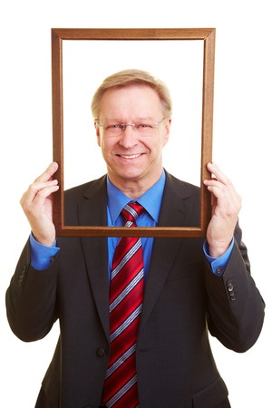 self conceit: Smiling senior businessman looking through an empty picture frame