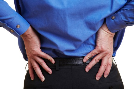 senior pain: Elderly businessman holding his hand to his aching back