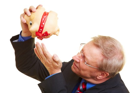 Senior businessman shaking an empty piggy bank photo