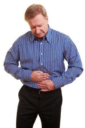 bowel: Elderly man holding his hands over his aching stomach Stock Photo