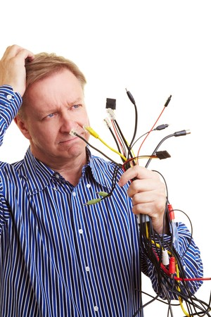 Elderly man with many different cables in his hand looking perplexed photo