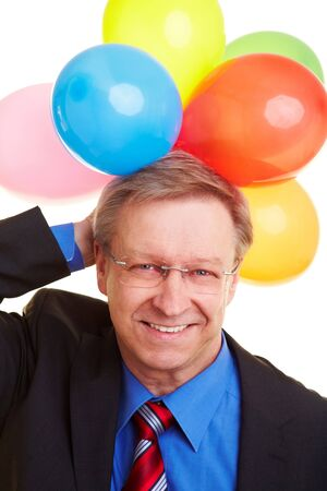 Happy senior businessman holding many colorful balloons photo