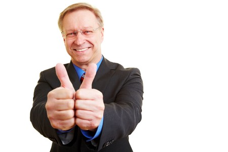 Senior businessman in a suit holding his thumbs up Stock Photo - 7540391