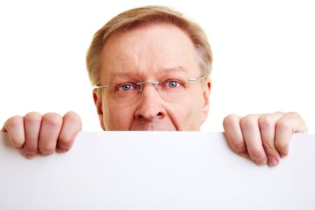 Surprised senior businessman peeking behind a white border photo