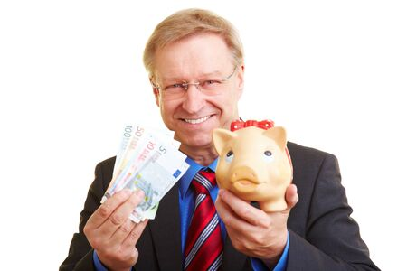 Smiling senior businessman holding piggy bank and banknotes Stock Photo - 7540400