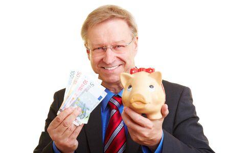 Smiling senior businessman holding piggy bank and banknotes photo