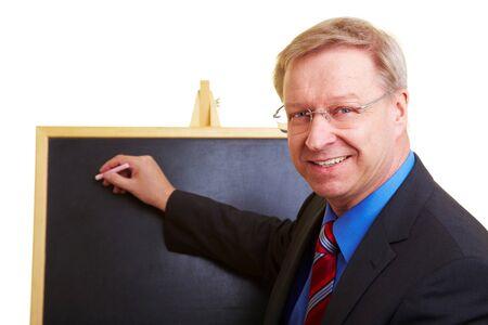 spokesman: Happy teacher standing in front of a black chalkboard