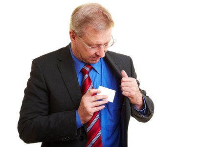 Senior businessman putting a business card in his pocket photo