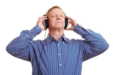 Elderly man listening to music with headphones photo