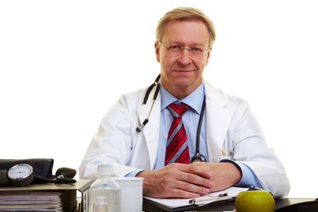 Friendly senior doctor sitting at his desk Stock Photo - 7540427