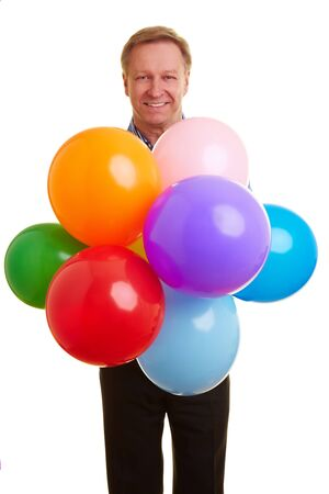 Happy elderly man with colorful balloons celebrating his birthday photo