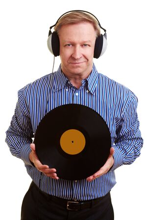 Elderly man with headphones holding an old record photo