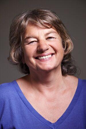 Happy female elderly citizen smiling into the camera photo