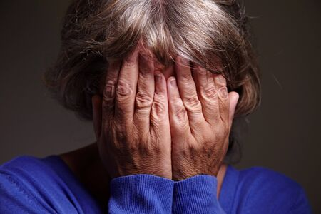 An elderly woman crying with hands in front of her head