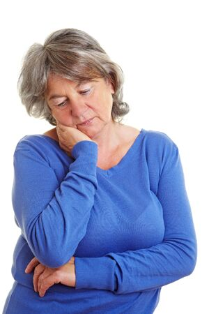 concerned: Sad retired woman with gray hair looking down Stock Photo