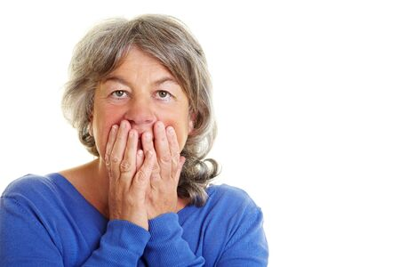 cutout old people: Frightened Retired woman holding hands over her mouth Stock Photo