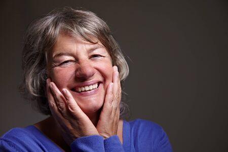 ancianos felices: Contenido jubilado femenino con las manos en su rostro una sonrisa