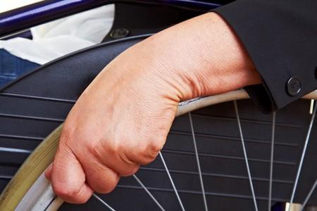 paraplegic: Manos arrugadas aferr�ndose a una silla de ruedas  Foto de archivo