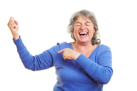 Happy female senior citizen showing her muscles Stock Photo - 7751925