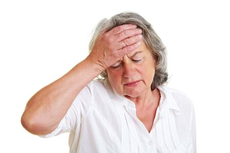 hand on forehead: Pensive elderly woman holding hand to her forehead