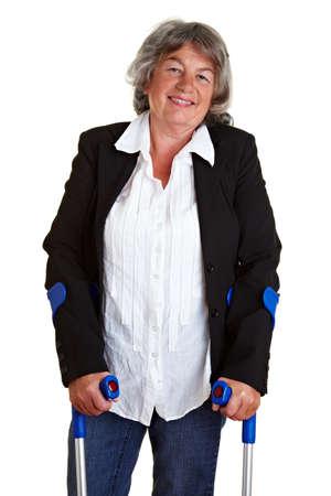 paraplegia: Smiling elderly woman walking with two crutches Stock Photo