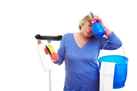 Frustrated retired woman holding many cleaning supplies photo