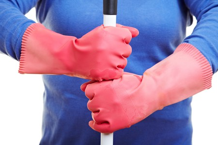 Red rubber gloves holding stick of a broom