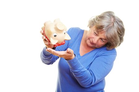 broke: Concerned retired woman shaking a piggy bank Stock Photo