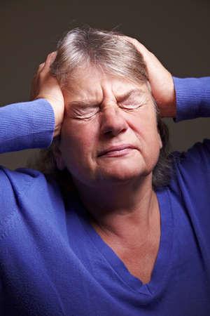 pangs: Senior donna con emicrania premendo le mani per la testa