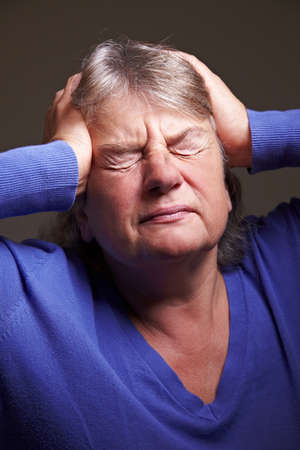 Senior woman with migraine pressing hands to her head photo