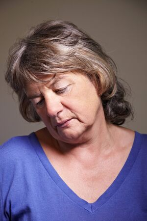 saddened: Sad elderly woman looking down with head tilted Stock Photo