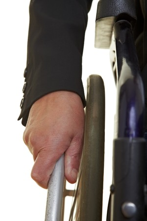 paraplegia: Wrinkled old hand pushing an push rim wheelchair