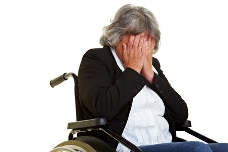 mobility nursing: Sad elderly wheelchair user holding hands in front of her face