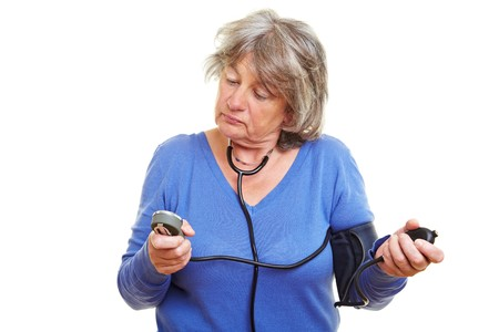 Elderly woman with gray hair measuring her blood pressure photo