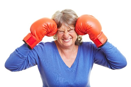 pangs: Elderly woman pressing red boxing gloves to her head Stock Photo