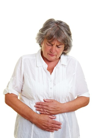 convulsions: Elderly woman with gray hair holding her aching stomach