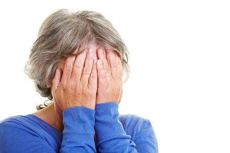 obscured: Worried elderly woman holding hands in front of her face