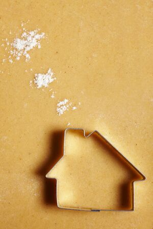 biscuit: Cookie cutter house on dough with flour clouds Stock Photo
