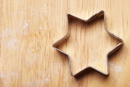 Cookie cutter in the shape of a star on wood photo