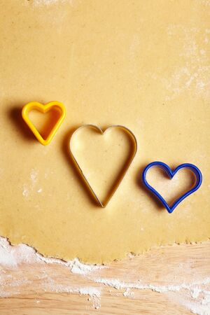 Three cookie cutters on dough with a heart shape photo