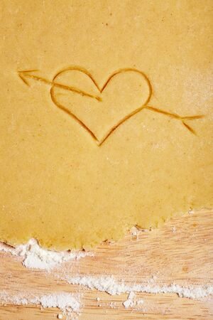 Heart with arrow carved in dough as a sign of love photo