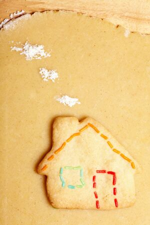 Cookie in shape of house on dough with flour as clouds photo