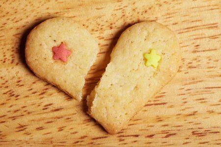 lovesickness: Broken decorated cookie heart on wooden base